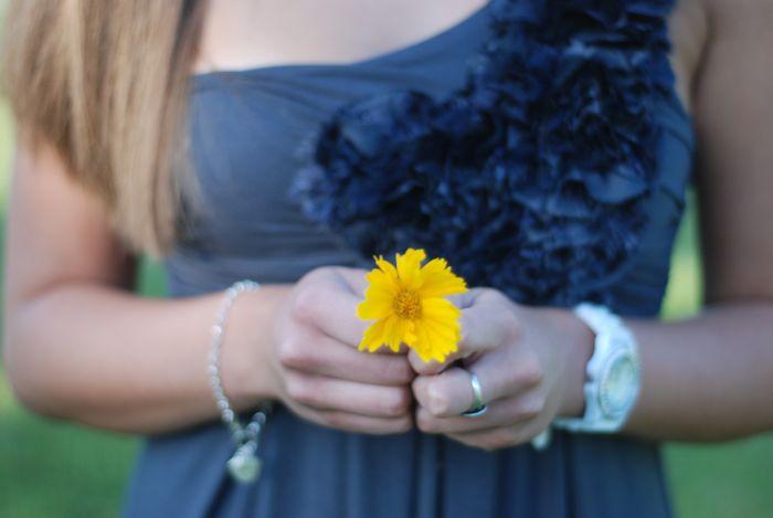 girl holding yellow flower